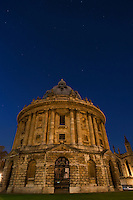 Stars appear as tiny dots of light above Oxford's Radcliffe Camera at night.