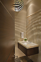Guest bath has onyx stone wall highlighted with patterns from the chandelier