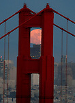The full moon rises over the BanK of America building in San Francisco while being framed by the north tower of the Golden gate Bridge one evening in San Francisco, California.