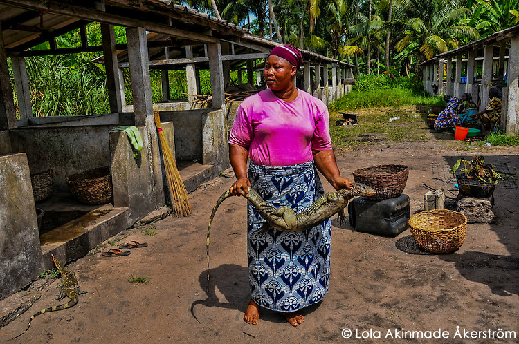Nigeria - Fishmonger shows off her prized monitor lizard captured the same morning.