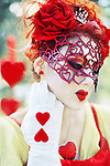 A pale young woman with red hair wearing a diamonte crown with heart lips and a heart mask with a red rose