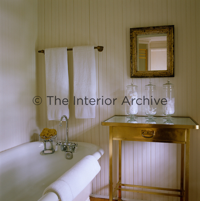 The simple bathroom has a clapboard wall and a brass table with a glass top