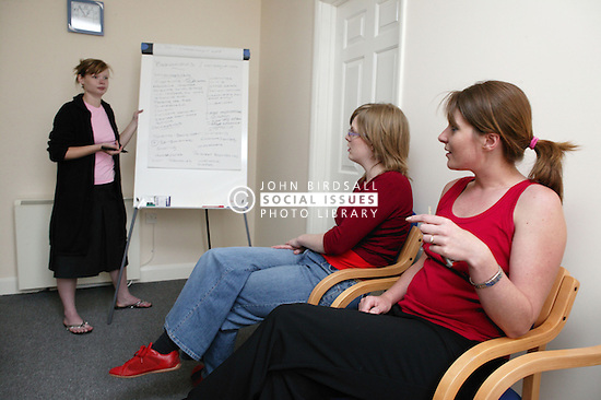 Woman tutor using flip chart during training session for project workers,