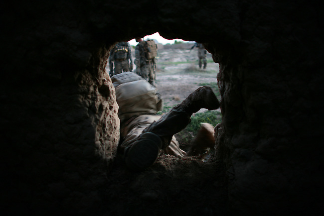 An Afghan soldier goes through a hole in a mud-brick wall surrounding an orchard during a patrol with U.S. forces in the Arghandab valley, near Kandahar, Afghanistan. March 27, 2010. DREW BROWN/STARS AND STRIPES