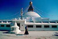 Nepalese woman walking past Bouddhanath Stupa in Nepal at the Kathmandu Valley World Heritage Site.