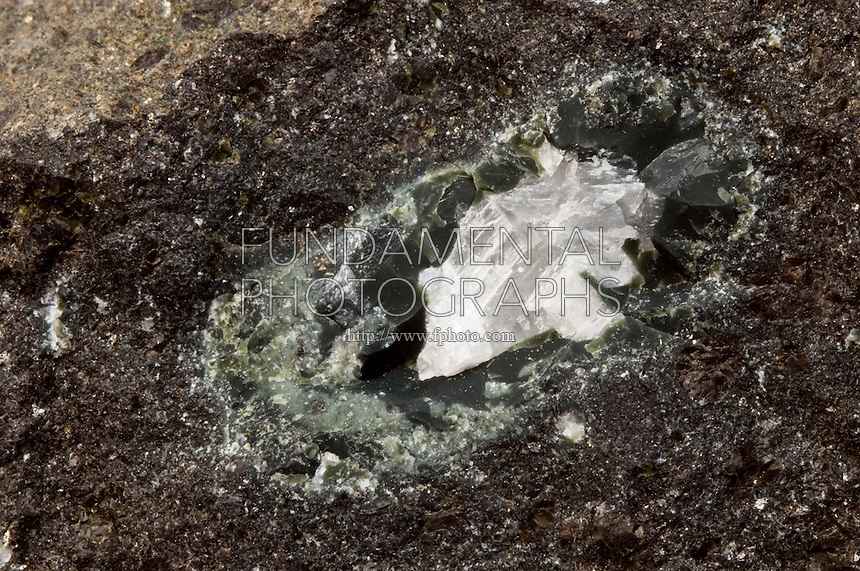 DIAMOND IN KIMBERLITE<br /> Potassic Volcanic Rock with Diamond<br /> Diamond taken from Sloan Mine, Larimer County, Colorado. Kimberlite occurs in the Earth's crust in vertical structures that are a large source of mined diamonds. The depth kimberlite is often found at contributes to diamond xenocrysts.