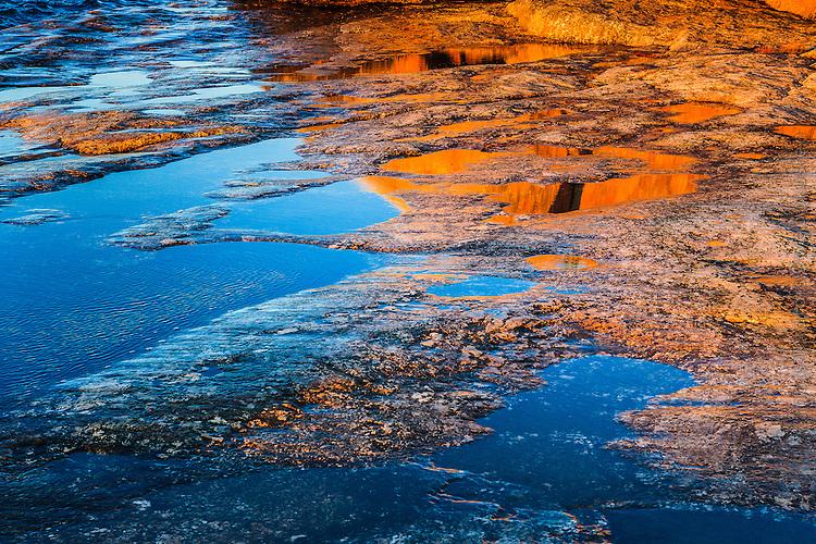 Spegling av röd klippa vid solnedgång i Stockholms skärgård. / Reflection of red rock at sunset in the archipelago Sweden.