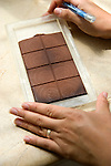 Worker checking chocolate quality in factory in Ecuador
