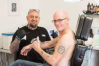 STORY BY STEVEN MORRIS SWANSEA, UK. 5th July 2015. Mike Thomas from Swansea Tattoo Lab tattoos a customer.