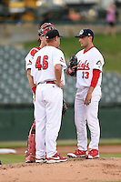 Peoria Chiefs pitcher Rob Kaminsky (33) listens to pitching coach Jason Simontacchi (46) with catcher Carson Kelly (19) during a game against the Kane County Cougars on June 2, 2014 at Dozer Park in Peoria, Illinois.  Peoria defeated Kane County 5-3.  (Mike Janes/Four Seam Images)