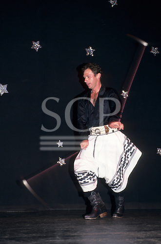 Buenos Aires, Argentina. Gaucho (cowboy) entertainer dancing on stage with boleadoras.