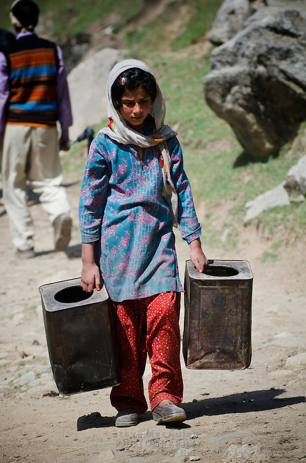 Young gypsy girl carrying large tin drums on trail above the Kanka River, near Naranag, Kashmir, India.