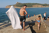 - bathing young people and veiled woman on waterfront of Tabarka town....- giovani bagnanti e donna velata sul lungomare della città di Tabarka