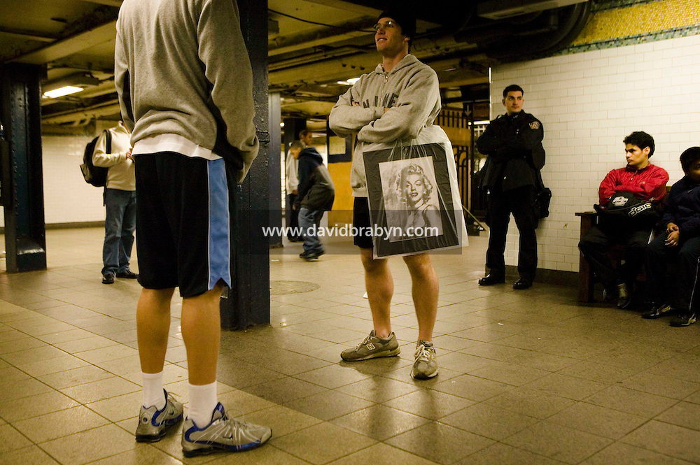 22 January 2006 - New York City, NY - Subway passengers wearing shorts wait for a train as a police officer looks on shortly after several participants in the 5th annual No Pants Subway Ride were arrested on the same platform for traveling on the #6 line without pants on in New York City, USA, 22 January 2006. The artists and pranksters of the Improv' Everywhere group organised the ride, which gathered over 150 participants, in order to surprise and amuse other passengers and themselves. The police issued summons and handcuffed several participants. Photo Credit: David Brabyn.