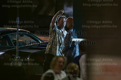 US actor Bruce Willis (R) is being prepared on set during a shooting of his next movie fifth in the Die Hard series titled Good Day to Die Hard in Budapest, Hungary on July 10, 2012. ATTILA VOLGYI