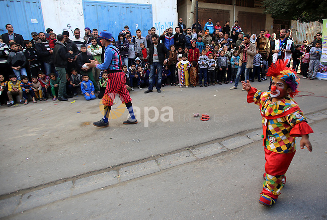 Clowns perform in front of Palestinian children during a street game organised by volunteers of the Friday of Joy Initiative, in al-Shati refugee camp, in Gaza city, February 6, 2015. Ten Palestinian volunteers organise street games, painting and drama, every Friday afternoon in the streets of  refugee camps and provide outlets for the children's energy with organised games, dancing and singing, which gives extra psycho-social support to vulnerable children. Photo by Khaled al-Sabbah
