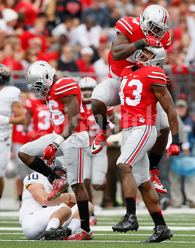 Ohio State Buckeyes linebacker Darron Lee (43) celebrates with Ohio State Buckeyes linebacker Curtis Grant (14) after sacking Kent State Golden Flashes quarterback Colin Reardon (10) during Saturday's NCAA Division I football game at Ohio Stadium in Columbus on September 13, 2014. Ohio State won the game 66-0. (Dispatch Photo by Barbara J. Perenic)