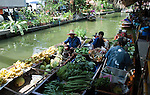 Bangkok - Thailand, February 25, 2012 -- Vendors on a floating market in Ladmayom, offering fruits and vegetables from their boat; people, small scale business, commerce, economy -- Photo © HorstWagner.eu