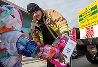 NWA Media/JASON IVESTER --12/17/2014--<br /> Jimmy Henley, Springdale firefighter, delivers a toy on Wednesday, Dec. 17, 2014, outside the EOA Children&rsquo;s House in The Pat Walker Center for Children in Springdale. The Springdale Firefighters Association, IAFF Local 3007, parterned with local businesses to collect toys for children in need for Christmas.