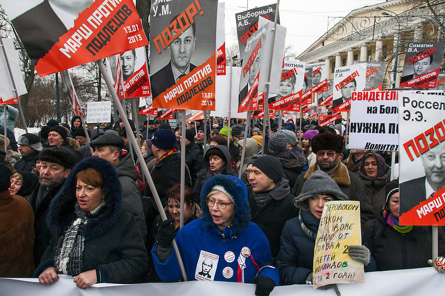 Moscow, Russia, 13/01/2013..People chant slogans as thousands of opposition protesters carry posters of President Vladimir Putin and members of the Russian parliament with the word ?Shame? written in red at a protest called the March Against The Scoundrels. The protest was against the new law banning the adoption of Russian children by Americans, widely seen as a response to the recently passed USA Magnitsky Act..