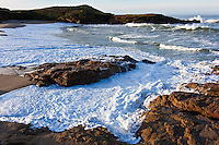 Incoming waves wash the sands and scrub the rocks at Bean Hollow State Beach, California.