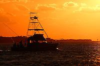 Fishing boat heading out into the Atlantic Ocean at dawn, Florida Keys.