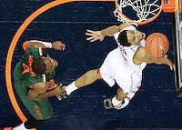 Virginia guard Malcolm Brogdon (15) shoots in front of Miami forward Raphael Akpejiori (4) during an NCAA basketball game Saturday Feb, 24, 2014 in Charlottesville, VA. Virginia defeated Miami 65-40.