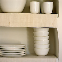 Detail of open shelving in the kitchen lined with linen cloths and housing stacks of simple white crockery