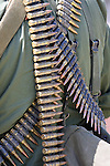 A military man carrying a belt of ammunition on his back male gun war machine army