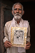 Karan, a former dacoit holds an old photo of the dreaded dacoit, Ghanshyam baba (surrounded by other dacoits) while he poses for a portrait outside the temple in Village Hanumangarhi, Dist - Jalaun, in Bundelkhand area of Uttar Pradesh, India. King of Rampura, Raja Keshwendra Singh (not seen in this picture) still enjoys the stature of a King in this modern day and age.