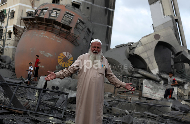 A Palestinian man reacts in front of the remains of a mosque, which witnesses said was destroyed in an Israeli air strike before a 72-hour truce, in Khan Younis in the southern Gaza Strip August 11, 2014. Israeli negotiators were due in Cairo on Monday for talks on ending a month-old Gaza war with Palestinian militants, an Israeli government official said, after a new 72-hour truce brokered by Egypt appeared to be holding. Photo by Ramadan El-Agha
