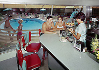 Waitress serving to couple at the Eden Roc Motel coffee shop that overlooks the pool. 1960's retro photograph.