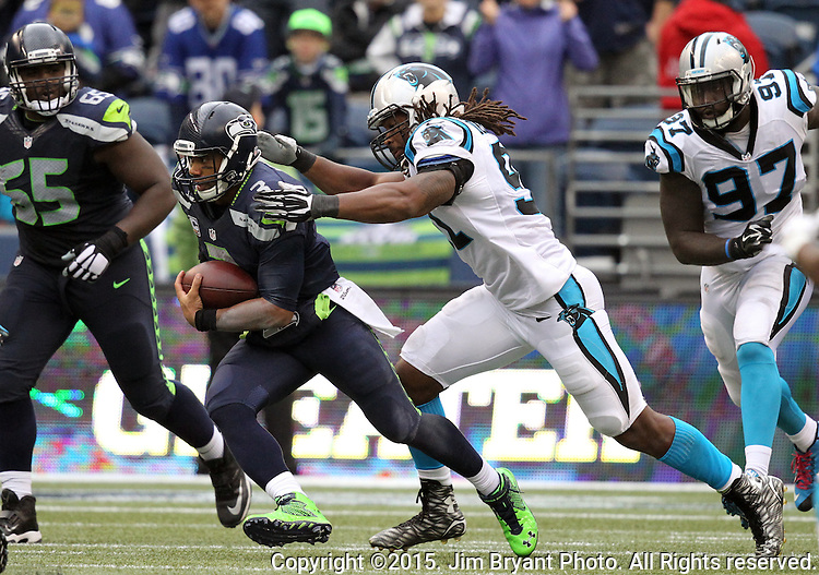 Seattle Seahawks quarterback Russell Wilson scrambles away from Carolina Panthers  defensive end Ryan Delaire (91) at CenturyLink Field in Seattle on October 18, 2015. The Panthers came from behind with 32 seconds remaining in the 4th Quarter to beat the Seahawks 27-23.  ©2015 Jim Bryant Photography. All Rights Reserved.