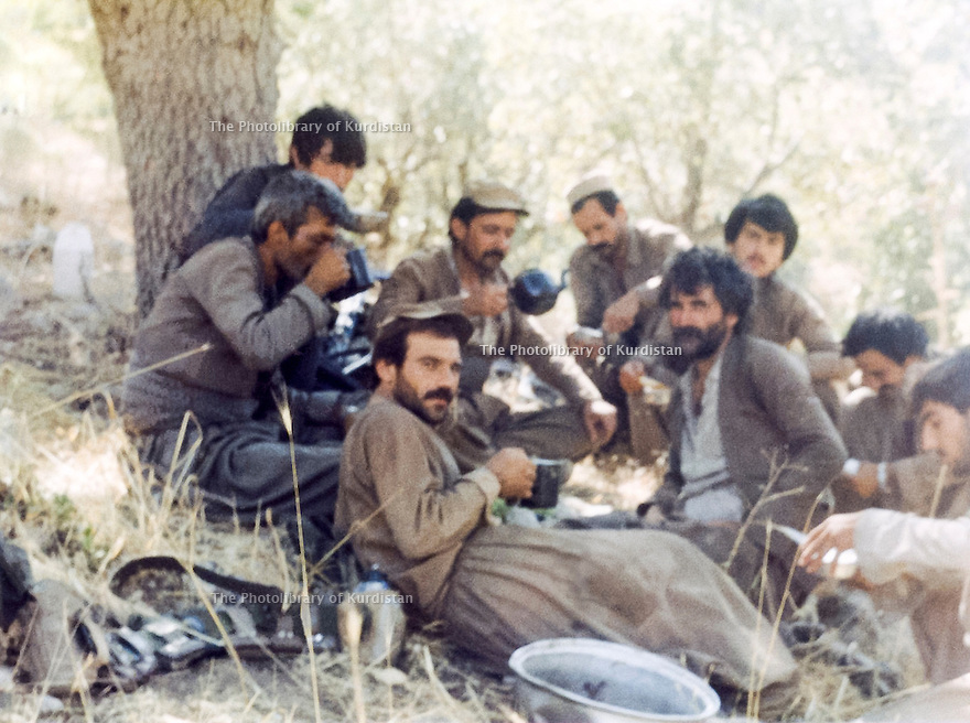 Iraq 1989.On july 2nd the peshmergas of Mahmoud Sangawi after 10 days walking from Iran arrive in Kopi Qara Dag and have a rest. In the middle, Mahmoud Sangawi drinking tea in the teapot.Irak 1989.Apres 10 jours de marche depuis l'Iran, le 2 juillet,les peshmergas de Mahmoud Sangawi arrivent a Kopi Qara Dag et se reposent. Au milieu d'eux, Mahmoud Sangawi boit du the dans une theiere
