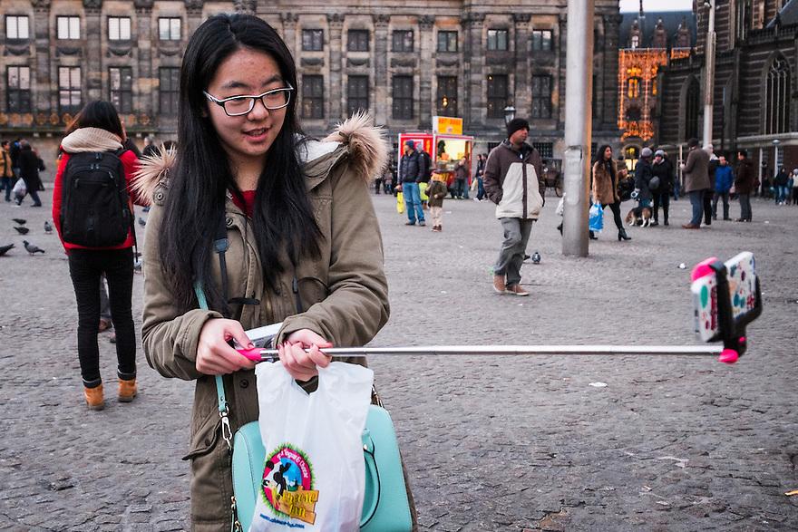 Nederland, Amsterdam, 31 jan 2015<br /> Chinese toeriste neemt een selfie met een speciaal voor selfies gemaakte stok, de Serlfie Stick,  om meer afstand te kunnen nemen.<br /> Foto: (c) Michiel Wijnbergh