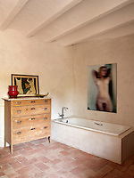 A contemporary photograph of a female nude and a contemporary bath have been installed in the otherwise rustic bathroom with bare walls  original terracotta tiled floor