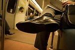 A Man dressed for business reads his newspaper while riding on the Metro in Washinton DC..His well polished shoe fills the foreground.