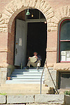 MAN RELAXES WITH BOOK ON STEPS OF COLORADO BUILDING