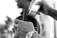Negro Youth Receiving a haircut and peeking around the barbers hand