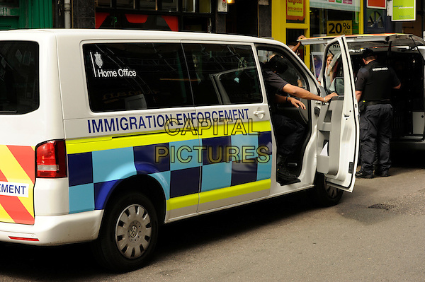 **Exclusive**<br /> Officers<br /> Immigration Enforcement offers took an alien from The Breakfast Club cafe in Soho, London, UK, 8th August 2013.<br /> **Exclusive All-Rounder**<br /> full length arrested arrest UK Boarder Agency politics police policing government van <br /> CAP/IA<br /> &copy;Ian Allis/Capital Pictures