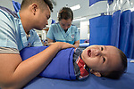 Ten-month old Johan gets an IV inserted in his hand by Nurse Jazmine Gino-Gino in the emergency room of the Mary Johnston Hospital in Manila, Philippines. Holding the boy down is Nurse Brian Grape Maningding. <br /> <br /> The hospital is supported by United Methodist Women.