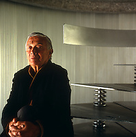 A portrait of architect Agustin Hernandez sitting on a  steel spiral staircase