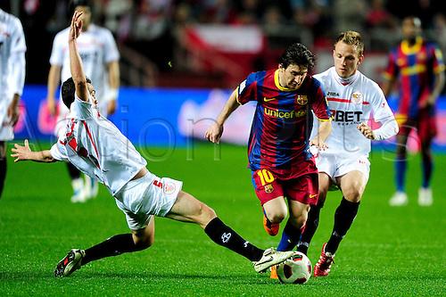 13.03.2011 Spanish La Liga Sevilla v Barcelona from Ramon Sanchez Pizjuan. Picture shows Fernando Navarro (Sevilla FC) Lionel Messi (FC Barcelona) Ivan Rakitic (Sevilla FC).