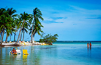 Dominikanische Republik, Punta Cana Beach Resort: Strand, Paar watet durchs Wasser | Dominican Republic, Punta Cana Beach Resort, beach, deck-chairs, couple standing in water