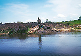 BOTSWANA, Africa, a lone man with his dugout canoe standing on the edge of the Zambezi River
