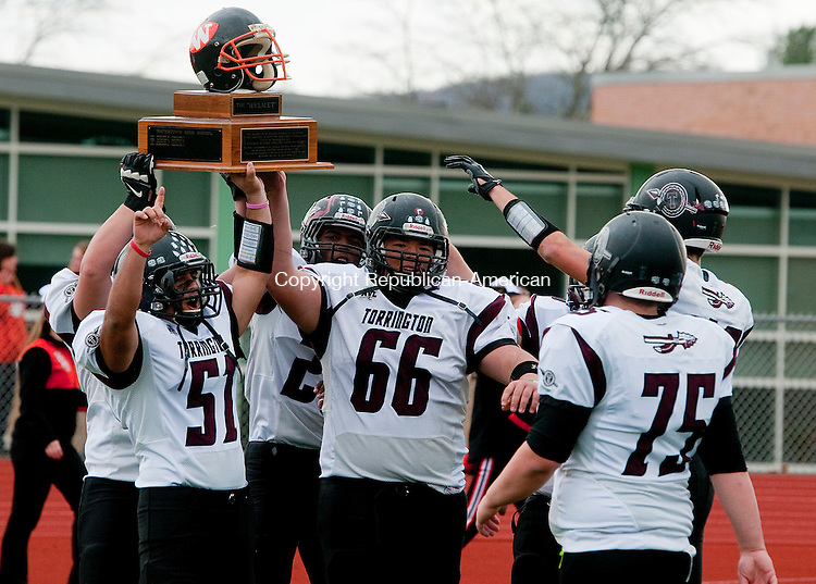 WATERTOWN, CT--- -112265JS26-Members of the Torrington football team hoist &quot;The Helmet&quot; trophy following their 52021 win over Watertown during their annual Thanksgiving day game Thursday at Watertown High School. <br /> Jim Shannon Republican-American
