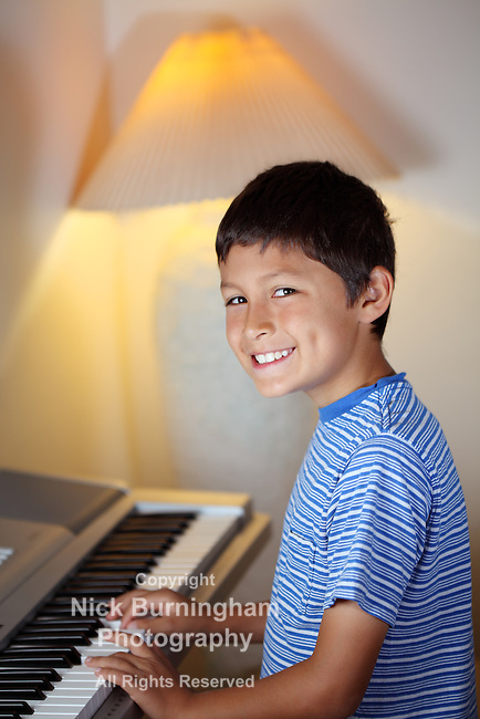 Yong boy plays on an elecrtonic piano keyboard