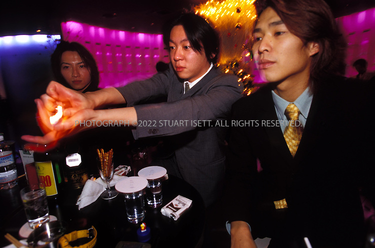 10/10/2003--Tokyo, Japan..Male hosts at the Players Club in Tokyo's trendy Roppongi district, entertain women and offer to ligh a cigarette...All photographs ©2003 Stuart Isett.All rights reserved.