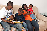 Family at home father and mother with sons ages 3, and 1 year old sitting on couch in living room father reading book to 3 year old while mother plays with baby horizontal