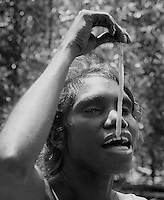 Tribal Aboriginal eating Mangrove worms, Arnhem Land Northern Territory, Australia